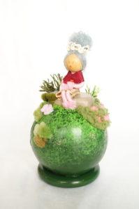 Objet décoratif avec planète miniature et personnage, mamie au jardin