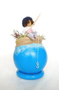 Objet décoratif avec planète miniature et personnage, pêcheur